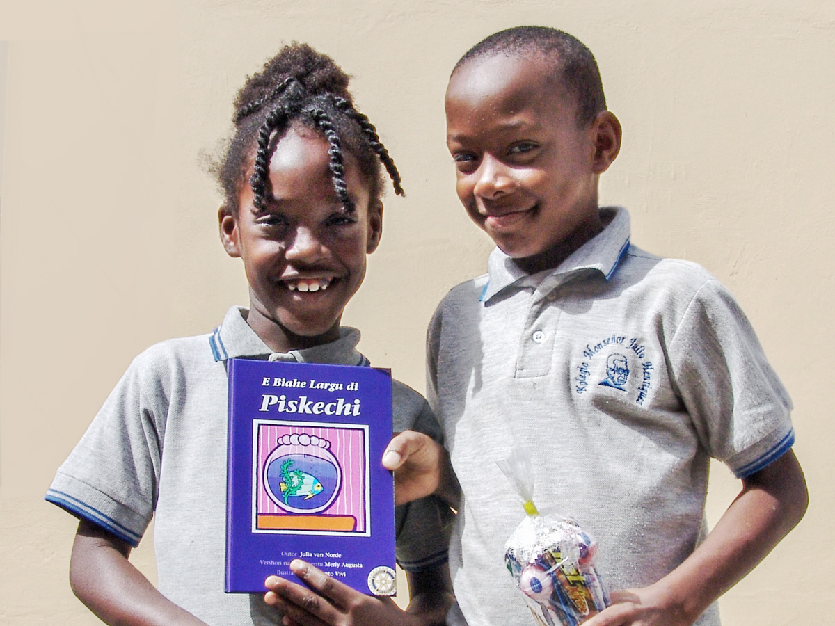2 school children showing picture book Piskechi